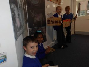 Some of the children from Hummingbird and Swan Classes showing items that they have made during our topic on the Stone Age.